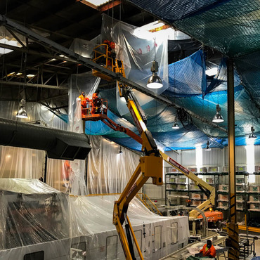 Debris and asbestos containment system incorporating fall arrest safety nets in live processing plant
